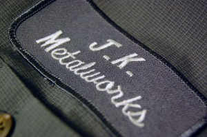 A stitched patch that reads JK Metalworks. It is on a work shirt.